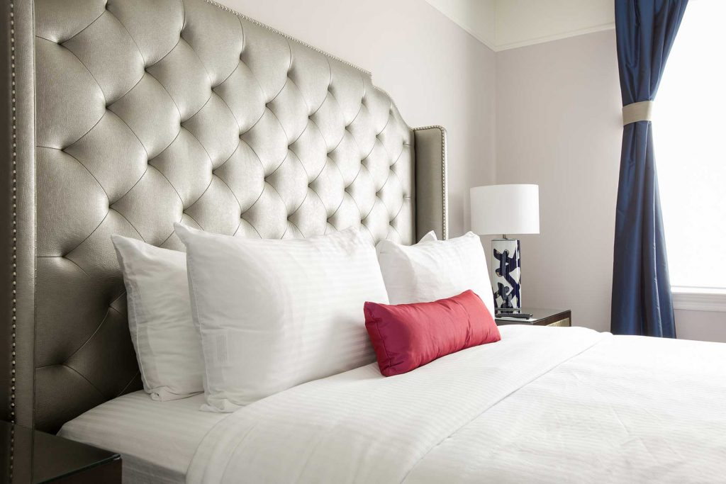 luxury hotel room bed with large leather headboard and red accent pillow
