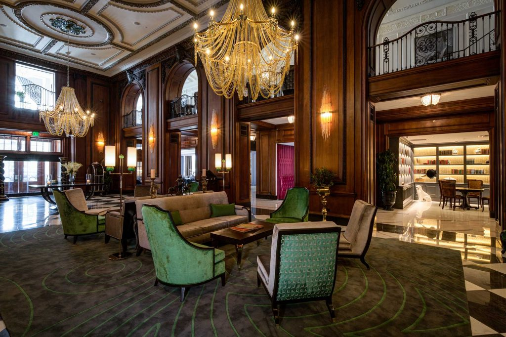luxury historic hotel lobby with green chairs and lavish chandeliers